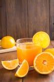 Szkło sok pomarańczowy z plasterkami na drewnianym tle obraz royalty free