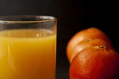 Szkło sok z trzy mandarynek pomarańczami nad czarnym tłem obraz stock