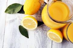 Szkło wapno sok i plasterki pomarańczowa owoc na drewnianym tle Obraz Royalty Free
