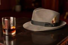 Szkło whisky i mężczyzna ` s kapelusz na drewnianym stole Zdjęcia Stock