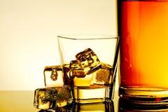 Szkło whisky z kostkami lodu pobliska butelka i kostkami lodu na stole z odbiciem, grże odcień atmosferę Fotografia Stock