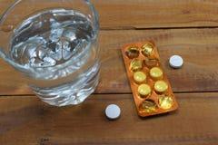 Szkło woda i pastylki na stole, doktorski ` s rozładowanie zdjęcia stock