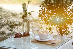 Szkło woda, kawa i okulary przeciwsłoneczni na stole z plenerowym zdjęcie stock