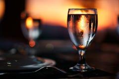 Szkło woda na stole z pięknym, kolorowym zmierzchem przy tłem, Obrazy Royalty Free