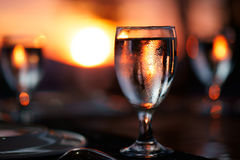 Szkło woda na stole z pięknym, kolorowym zmierzchem przy tłem, Obraz Stock