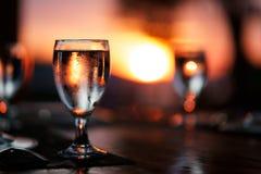 Szkło woda na stole z pięknym, kolorowym zmierzchem przy tłem, Obraz Royalty Free