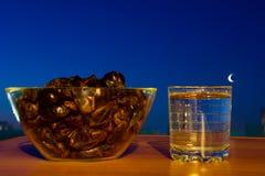 Szkło woda pitna, daty i księżyc, Podstawowy jedzenie i napój łamać Ramadan post fotografia royalty free
