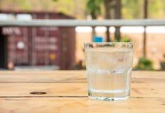 Szkło woda z lodem, kropli woda na szkle, drewniany stół Obrazy Stock