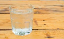 Szkło woda z lodem, kropli woda na szkle, drewniany stół Zdjęcia Royalty Free