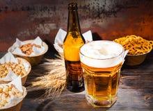 Szkło z świeżo polanym piwem i głową piankowa pobliska butelka i Zdjęcie Stock