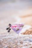 Szkło z chłodniczym napojem w pianie denna kipiel na plaży wśród otoczaków Zdjęcie Royalty Free
