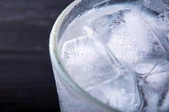 Szkło z kostkami lodu Czarny tło Makro- zdjęcie stock