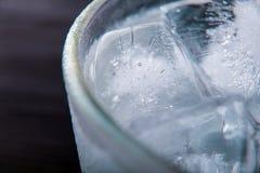Szkło z kostkami lodu Czarny tło Makro- zdjęcia stock