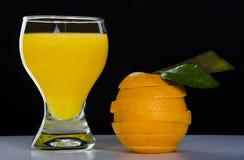 Szkło z sokiem pomarańczowym, rżnięta pomarańcze Obrazy Royalty Free