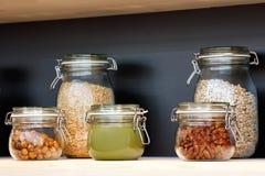Szkło zgrzyta z adrą, dokrętki, masło, dżem na drewnianej półce na tle zmrok ściana, śniadaniowy pojęcie, kuchenny tło, Obraz Stock