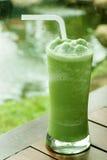 Szkło zielonej herbaty frappe na drewnianym stole w ogródzie fotografia stock