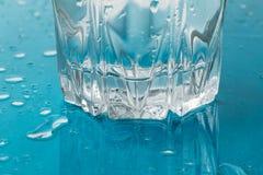 Szkło zimna woda z kroplami w błękicie i odbicie ukazujemy się Napój zdrowie świeżości aqua pojęcie Zdjęcia Royalty Free