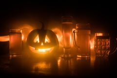 Szkło zimny lekki piwo z banią na drewnianym tle dla Halloween Szkło świeży piwo i bania na zmroku tonował mgłowych półdupki obrazy royalty free