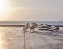 Szkła i lotosowego kwiatu lying on the beach na drewnianym stole Obraz Stock