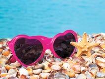 Szkła i skorupy na dennym piasku Zdjęcia Royalty Free