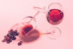 Szk?o czerwone wino na stole jest obracaj?cy do g?ry nogami i wi?zka winogrona na delikatnym r??owym tle Selekcyjna ostro?? obrazy royalty free