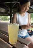 Szkło lodowa cytryny herbata i azjata kobieta Zdjęcia Stock