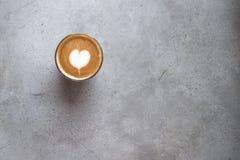 Szk?o smakowity latte z mi?o?ci sztuk? na betonie textured t?o obraz stock