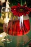 Szkło szampan obok szklanej wazy z kwiatami Obrazy Stock