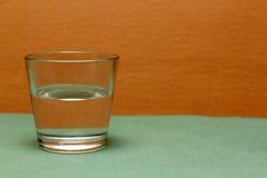 Szkło woda na barwionym tle Obrazy Stock