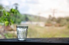 Szkło woda na drewnianym balkonie Fotografia Royalty Free