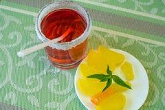 Szkło z napojem i spodeczkiem z owocowym cukierkiem zdjęcia stock