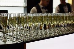 Szk?a szampan s? na stole W tle jest dwa kelner zdjęcie stock