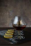 Szkła z koniakiem, cytryna plasterki z cukierem na drewnianym stole w tle Obrazy Stock