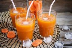 Szkła z marchwianym sokiem na drewnianym tle Fotografia Stock