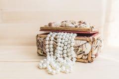 Szkatuła z perełkowymi koralikami na drewno stole Obrazy Stock
