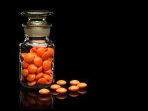 Szklana buteleczka z szklaną pokrywą i pigułkami pomarańczowi kolory. Fotografia Stock