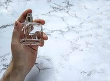 Szklana butelka męski pachnidło w ręce Obrazy Royalty Free