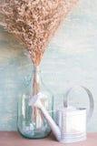 Szklana butelka wysuszony kwiat i podlewanie Obraz Stock