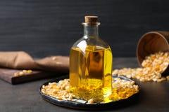 Szklana butelka z kukurydzanym olejem i wysuszeni nasiona na tle Zdjęcia Royalty Free
