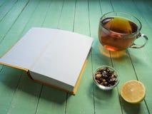Szklana filiżanka czarna herbata i otwarta książka na barwiącym drewnianym stole Zdjęcie Stock