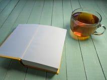Szklana filiżanka czarna herbata i otwarta książka na barwiącym drewnianym stole Obraz Stock