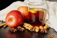 Szklana filiżanka gorący korzenny napój z, cynamon i anyż na brązu drewnianym tle jabłkiem i pomarańczowymi plasterkami, fotografia stock