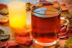 Szklana filiżanka herbaciana i rozjarzona świeczka na drewnianym stole z jesień liśćmi Obraz Royalty Free