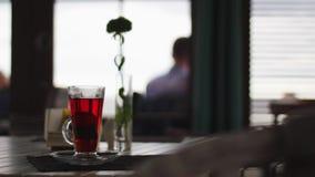 Szklana filiżanka herbata i mała waza z kwiatem umieszczają na stole przy restauracją zbiory wideo