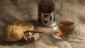 Szklana filiżanka herbata i spodeczek chlebowy braun cukier i cynamonowe rolki na bieliźnianym tle obraz royalty free