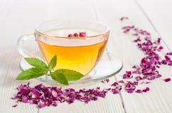 Szklana filiżanka herbata z nowymi i wysuszonymi różanymi płatkami Zdjęcia Royalty Free
