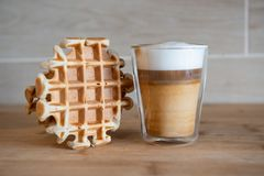 Szklana filiżanka multilayer kawa z mini stroopwafel, syrupwaffles ciastka na świetle - szary tło z kopii przestrzenią Fotografia Stock