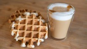 Szklana filiżanka multilayer kawa z mini stroopwafel, syrupwaffles ciastka na lekkim drewnianym tle z kopii przestrzenią Obrazy Royalty Free