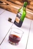 Szklana filiżanka z alkoholem i otwiera butelkę whisky Zdjęcie Stock