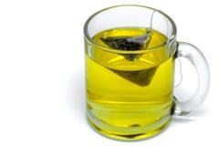 Szklana filiżanka z teabag, zielona herbata odosobniony miotła biel fotografia stock